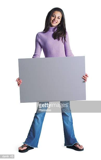 a cute ethnic female wearing jeans and a purple shirt stands with her feet shoulder width apart and holds a blank sign in front of her and smiles - girl wear jeans and flip flops stock photos and pictures