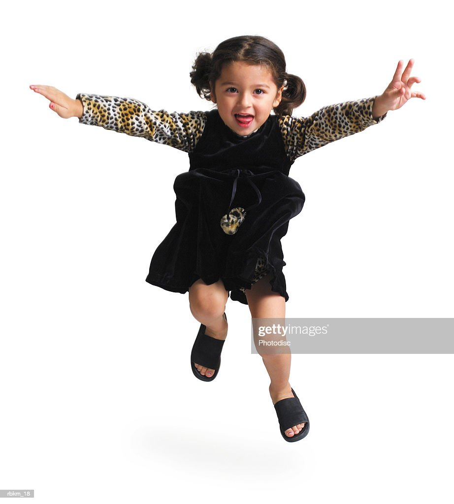 a cute ethnic looking girl in a black dress jumps up and throws her arms out : Stockfoto