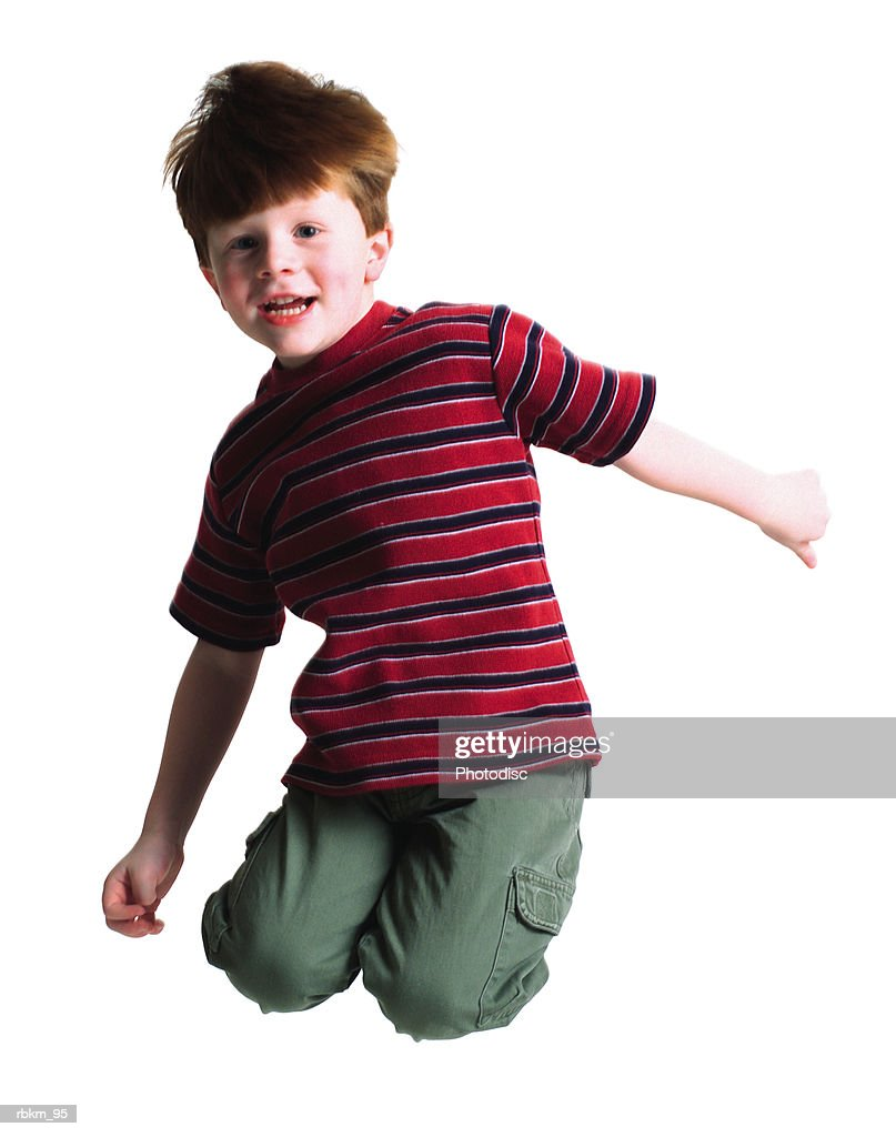 a cute littel redheaded boy jumps up high into the air and tuck his legs behind him : Stockfoto