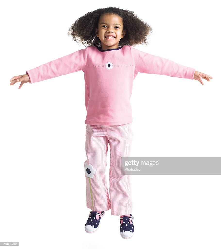 a cute little african american girl in a pink outfit jumps up and spreads out her arms : Stockfoto