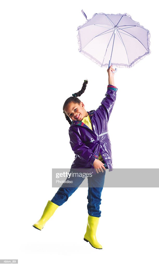 a cute little african american girl in a rain jacket jumps into the air with her umbrella : ストックフォト
