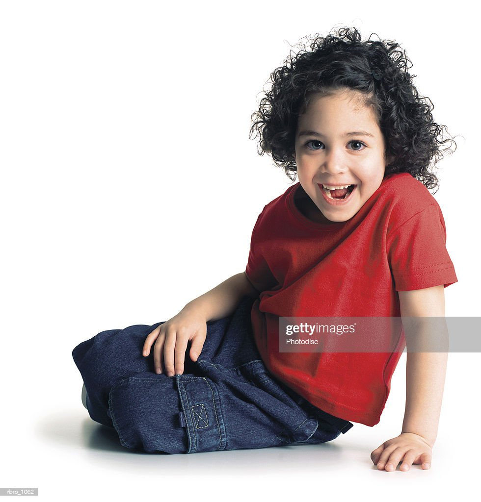 a cute little ethnic girl in a red shirt sits down and flashes a bright smile at the camera : Stockfoto