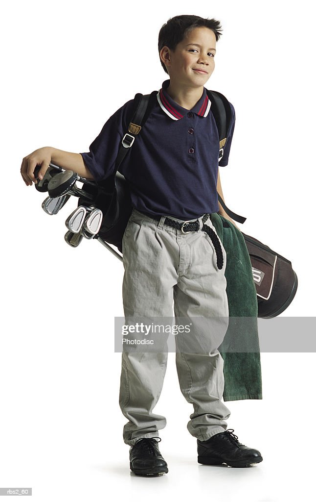 a cute polynesian boy stands smiling with his bag of golf clubs hanging on his shoulder behind him : Stockfoto