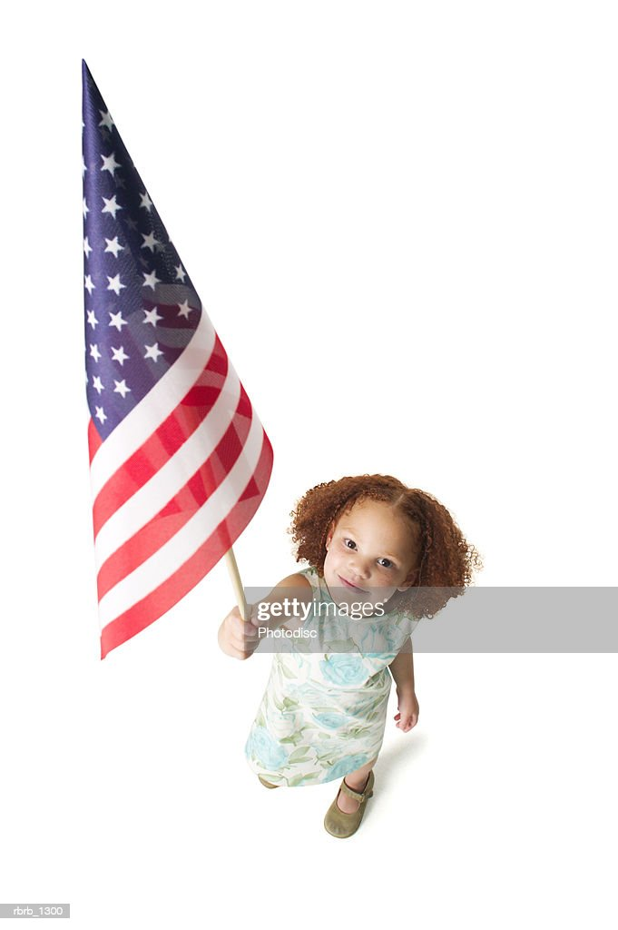 a cute redheaded female child in a green dress holds up an amercian flag to the camera : Stockfoto