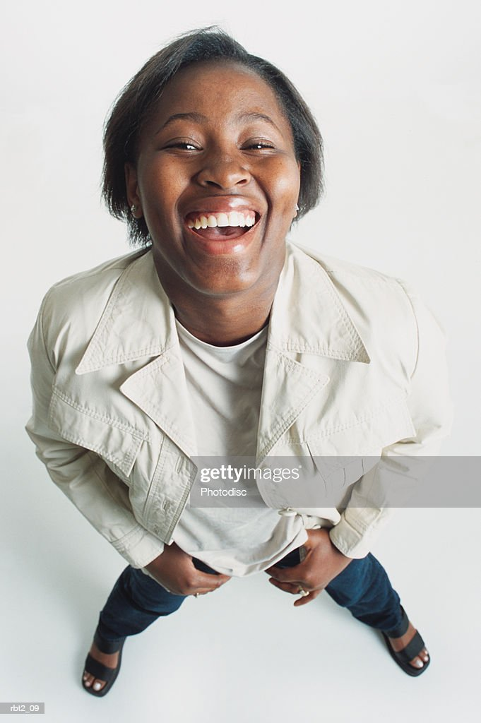 a cute teenage african american girl with short hair stands looking up at the camera laughing happily : Stock-Foto
