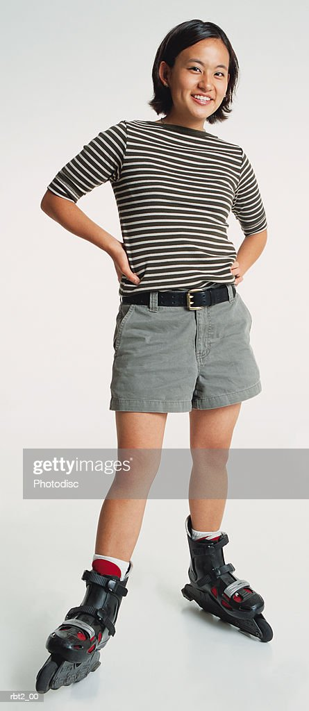 a cute young asian woman wearing roller blades and shorts stands smiling with hands on hips : Foto de stock