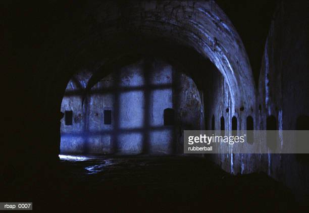 a dark castle hallway filled with eerie shadows - dungeon stock photos and pictures