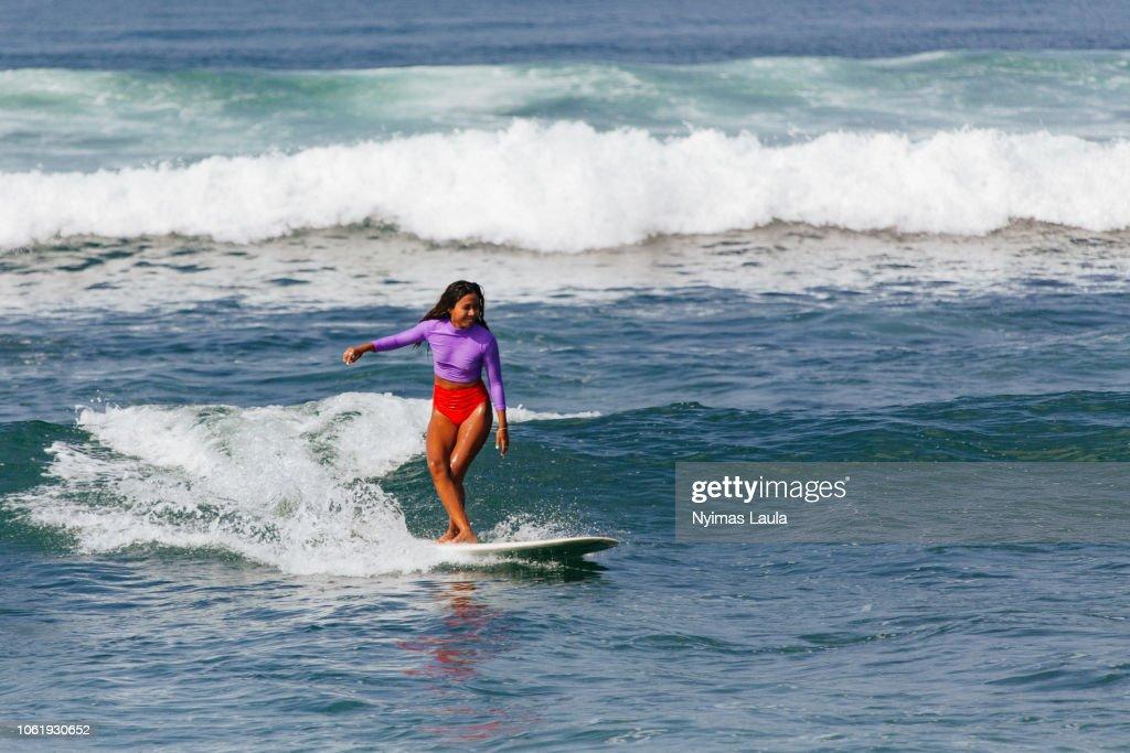 a dark skinned woman surfing : Stock-Foto