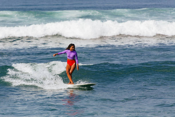 a dark skinned woman surfing