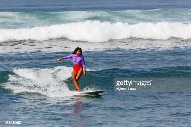 a dark skinned woman surfing