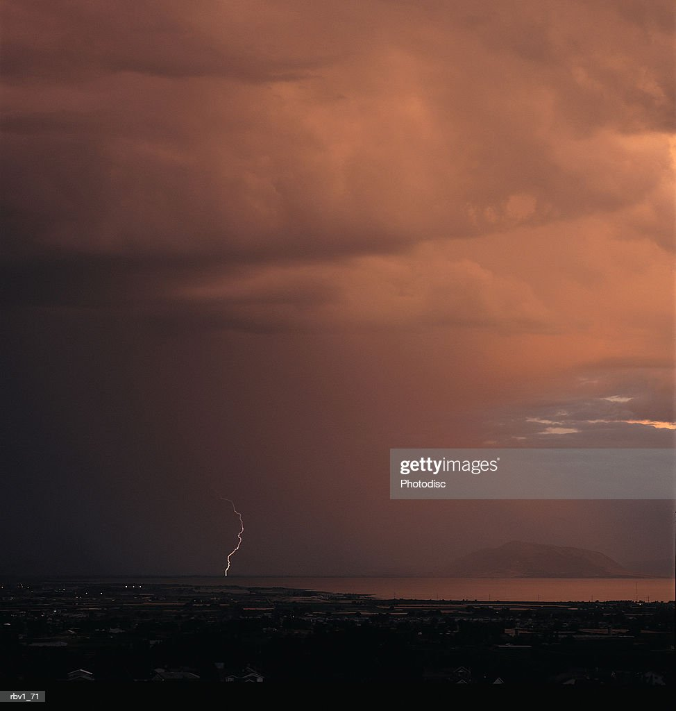 a darkly clouded sky releases a lightning bolt to the ground and body of water below : Foto de stock