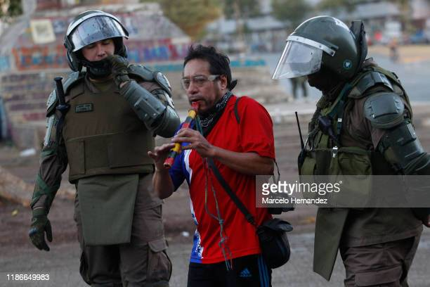 A demonstrator plays a quena as observed by riot police officers during the protests against president Sebastian Piñera at Plaza Italia on December...
