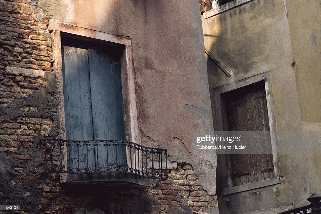 a doorway leading to a balcony from a stucco wall amongst other buildings : Foto de stock