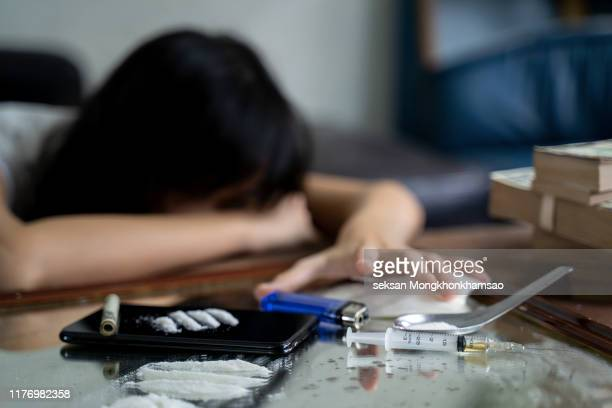 a drug addict with a syringe using drugs lying on the floor. the concept of anti drugs. male drug addict, drug syringe. - heroin stock pictures, royalty-free photos & images
