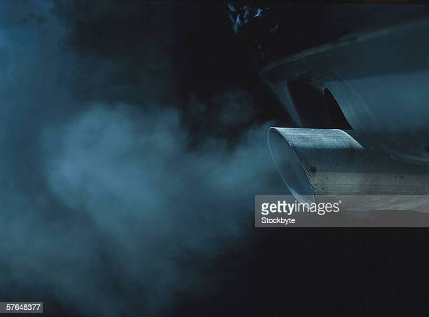 a exhaust pipe of a car emitting fumes - fumes stock photos and pictures
