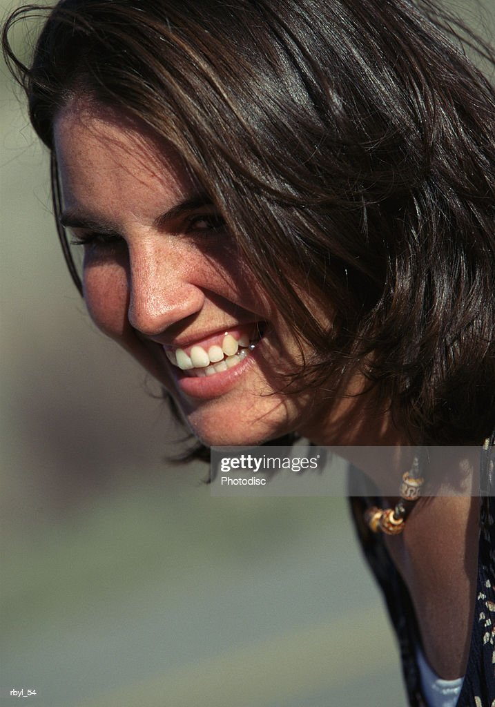 a face shot of a young woman with dark shoulder length hair smiling : Foto de stock