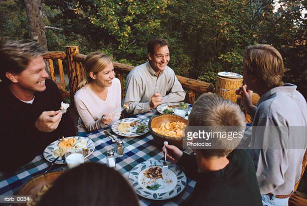 a family is sitting outside on a deck eating dinner together while laughing during the conversation - isla reunion fotografías e imágenes de stock