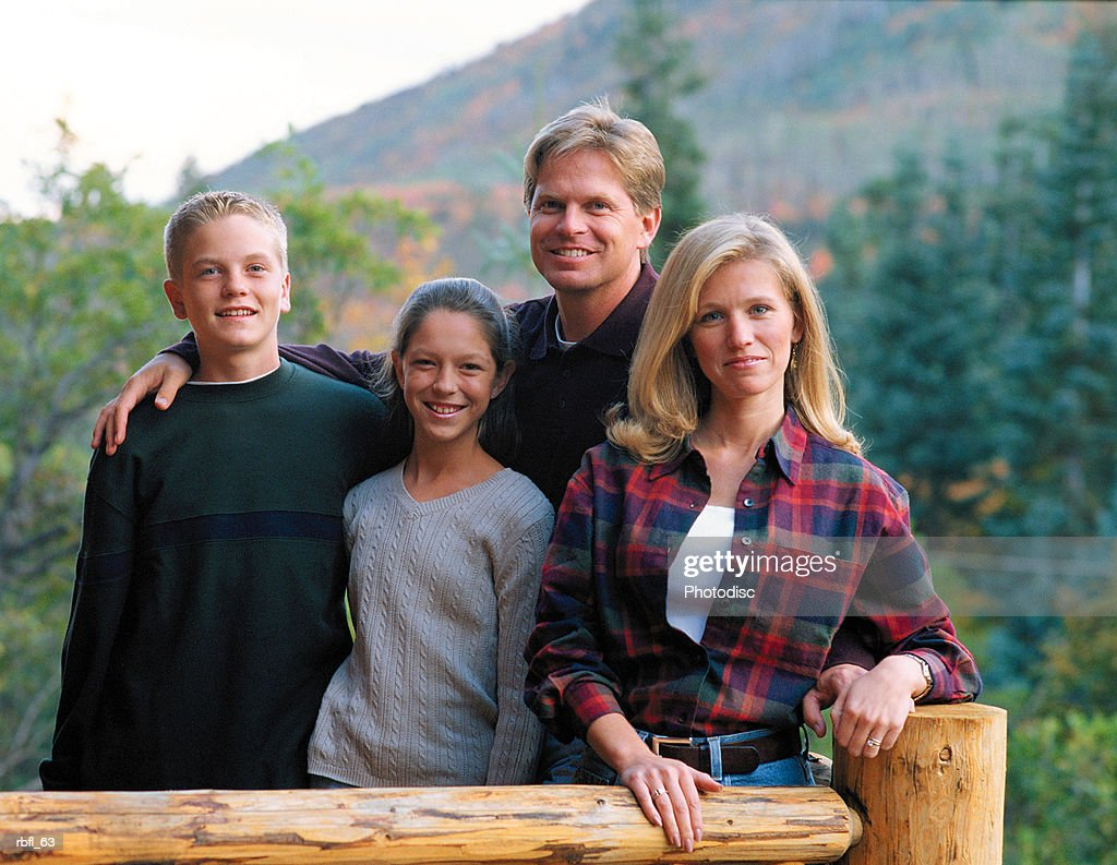 a family of four stands together on a cabin porch : Stockfoto