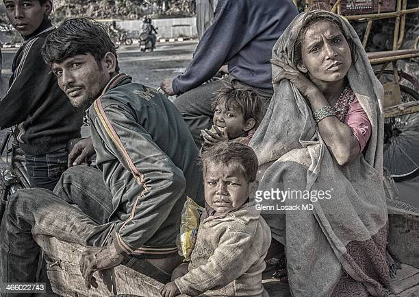 CONTENT] a family of lower caste woman man and children in a wooden wagon driven to their next hovel Loha Pule DELHI India