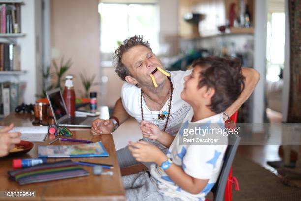 a family snacking on potato chips while sitting around the table at home. - making a face stock pictures, royalty-free photos & images