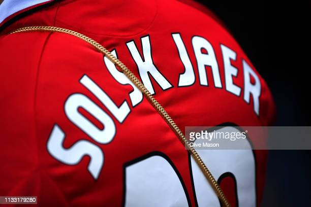a fan is seen with Ole Gunnar Solskjaer Interim Manager of Manchester United's name on the back of their shirt prior to the Premier League match...