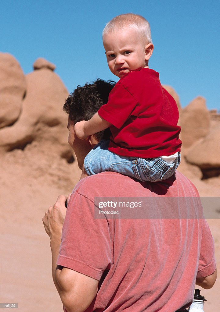 a father gives his toddler a piggy-back-ride through red rock desert : Stockfoto