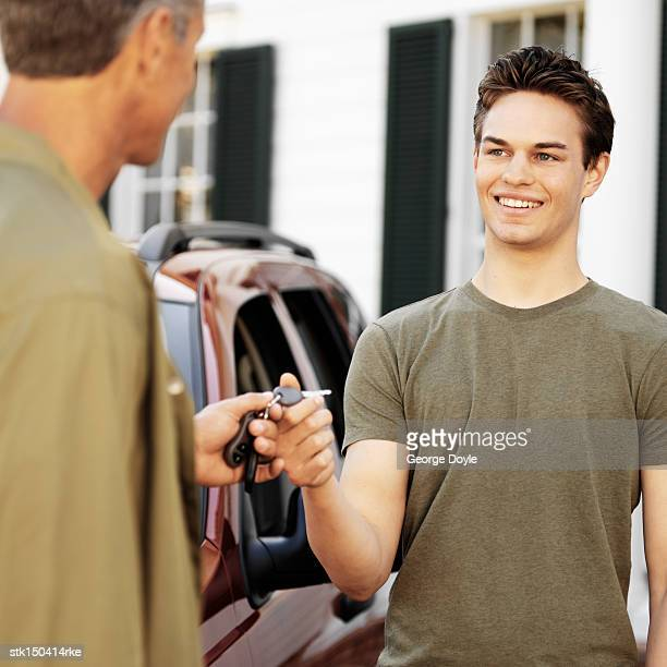 a father giving the cars keys to his son