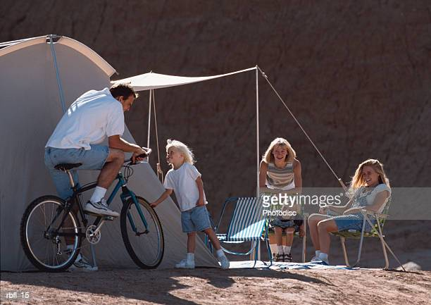 a father on his bicycle stops to talk to his daughters at their tent