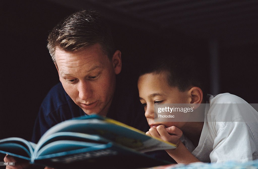 a father reads a book to his son laying on the bed : Stock Photo