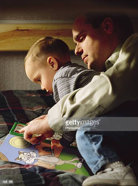 a father reads with his young son on the bed