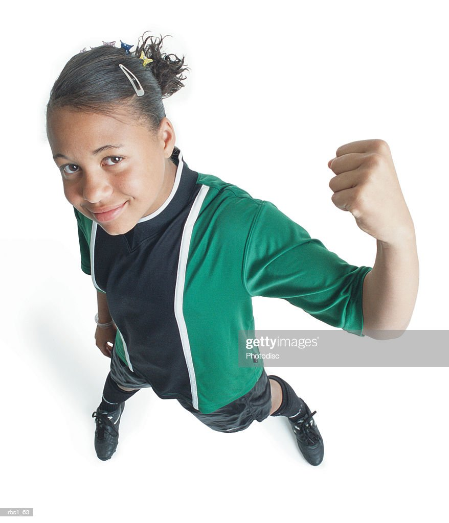 a female african american preteen soccer player in a green and black jersey celebrates a victory with her fist in the air as she smiles and looks up into the camera : Foto de stock