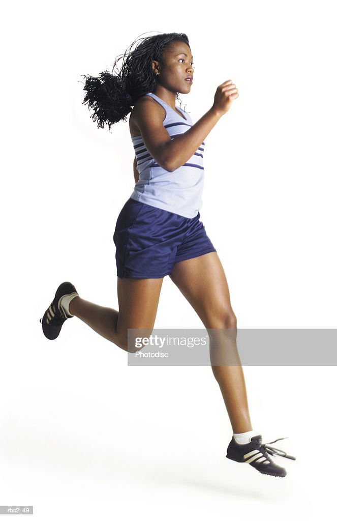 a female african american runner wearing blue has long hair as she jogs in profile to the camera : Foto de stock