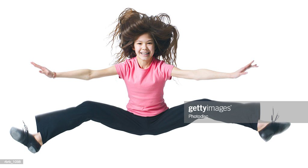 a female asian child in black pants and a pink shirt jumps up and kicks out her legs : Stockfoto