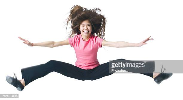a female asian child in black pants and a pink shirt jumps up and kicks out her legs - funny black girl ストックフォトと画像