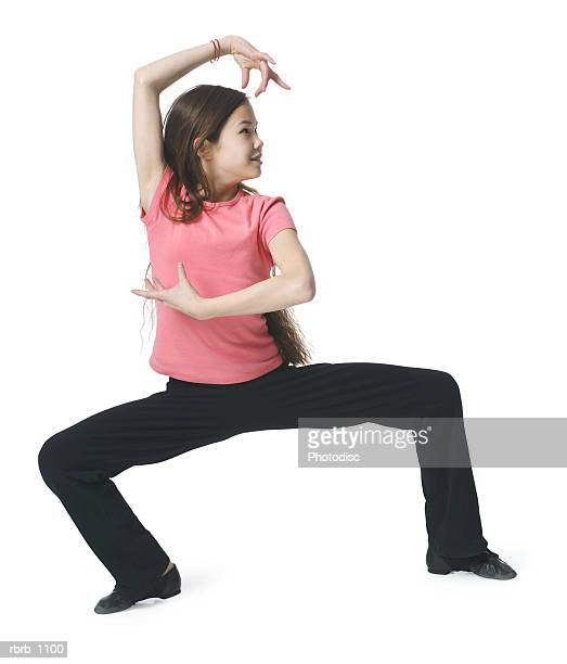 a female asian child in black pants and a pink shirt stikes a fun pose - funny black girl ストックフォトと画像