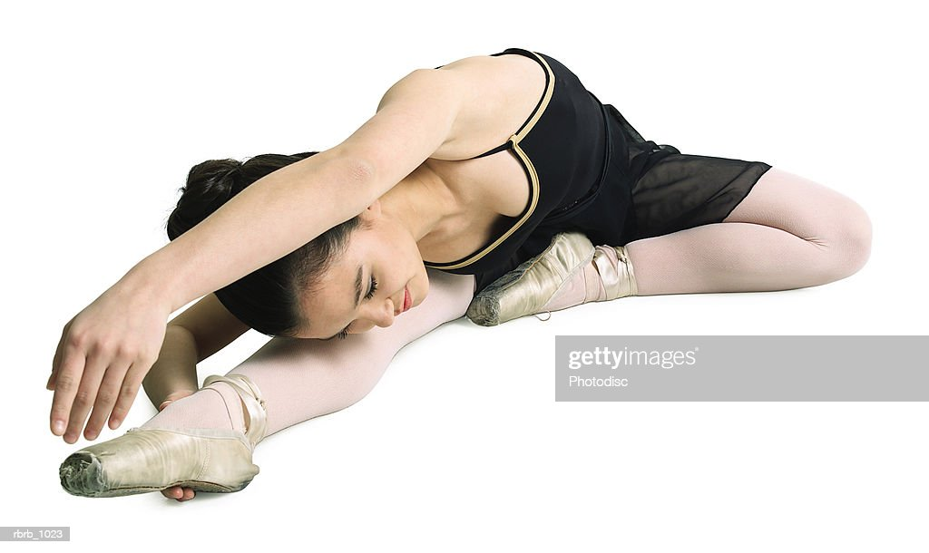 a female asian teenager in a black ballet outfit stretches out towards her toe : Stockfoto