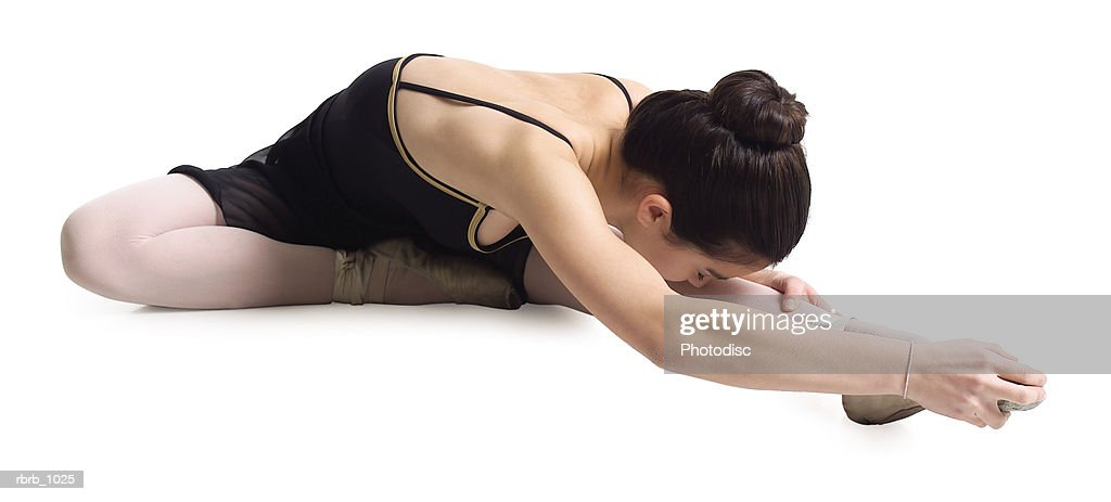 a female asian teenager in a black ballet outfit stretches out towards her foot in a ballet pose : Stockfoto