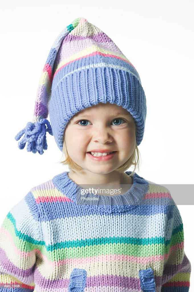 a female caucasian child in a colorful winter sweater and hat smiles brightly : Stockfoto
