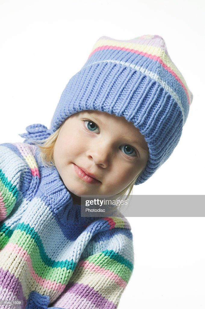 a female caucasian child in a colorful winter sweater and hat smiles slightly : Stockfoto