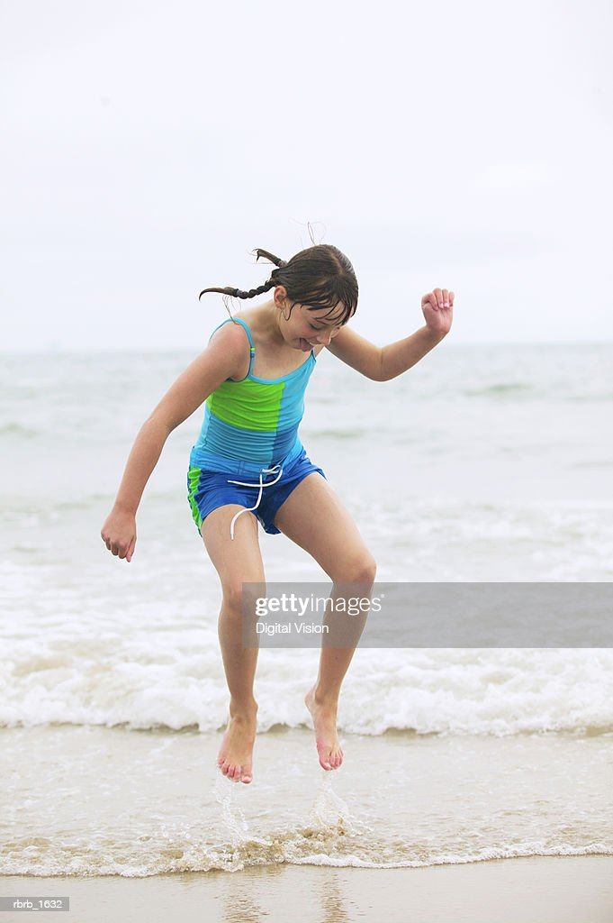 a female caucasian child in a green swimsuit dances and plays in the waves at the beach : Stockfoto