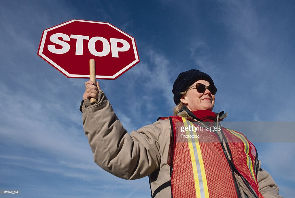 a female caucasian wearing sunglasses and a wool cap holds a stop sign at a crosswalk : Foto de stock