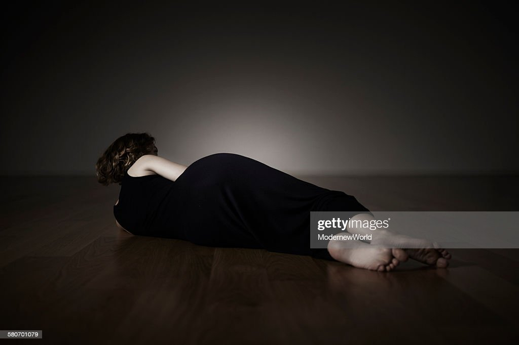 a female lying on the floor : Stock Photo