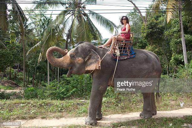 a female tourist rides an elephant