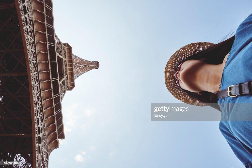 a female tourist under Eiffel Tower : Stock Photo