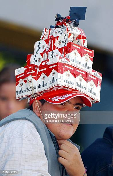 a Ferrari fan wears a hat made of Marlboro pack of cigarettes on the Monza racetrack during the warm up 16 September 2001 before the Italian Formula...