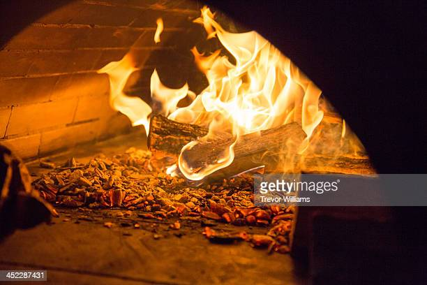 a fire inside a stone oven - firewood stock pictures, royalty-free photos & images
