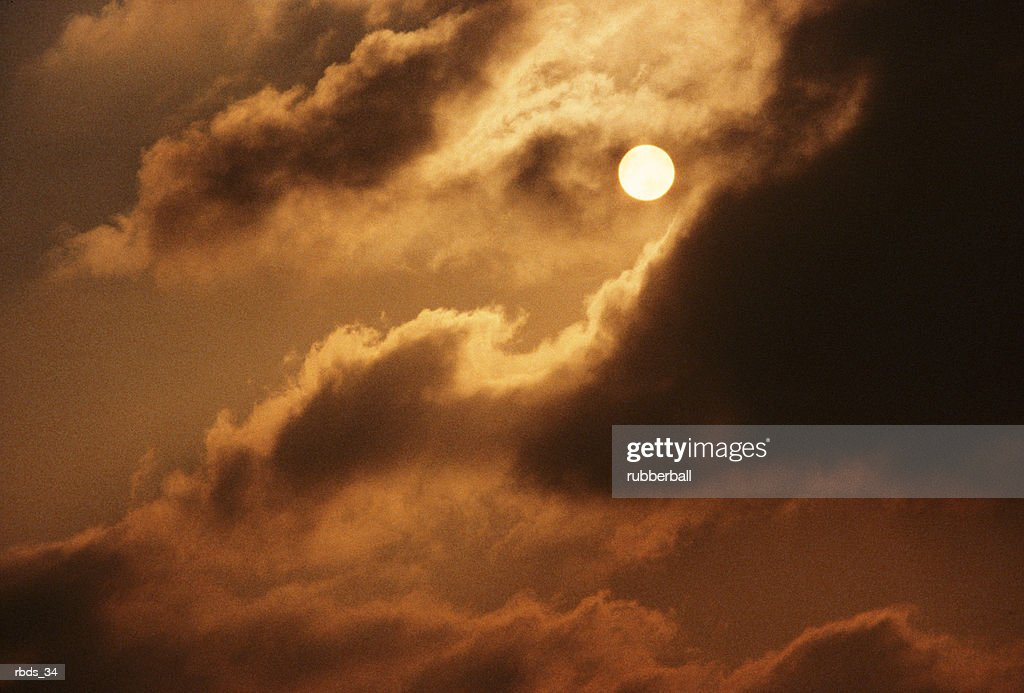 a full moon peaks out from behind a cloud covering with a warm glow : Stockfoto