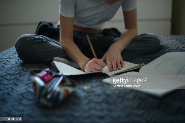 a girl doing schoolwork from home during corona lockdown. she is sitting comfortably on a bed and doing exercise work in math - kristina strasunske stock pictures, royalty-free photos & images