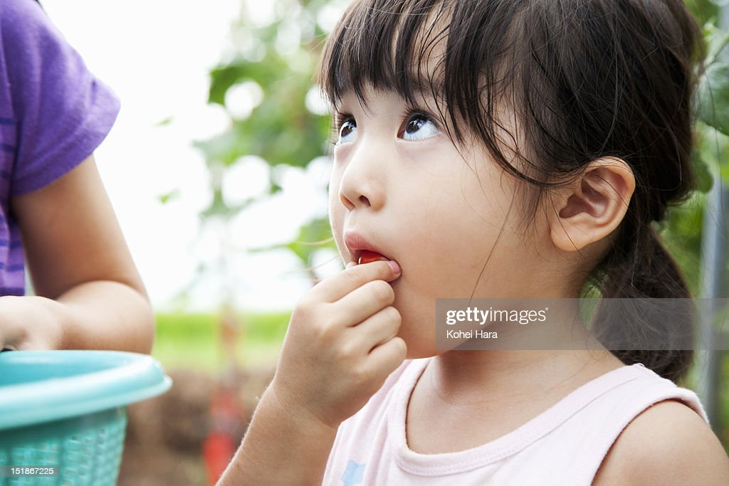 a girl eating a cherry tomato in the farm : Stock Photo