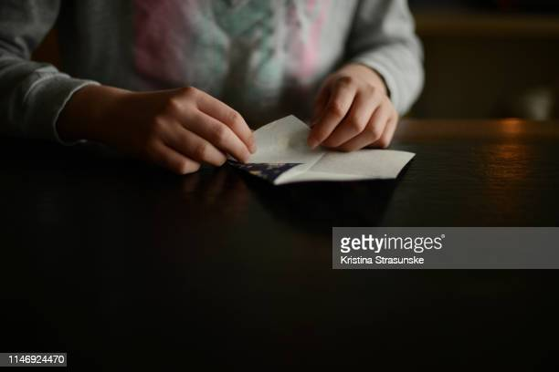 a girl folding origami paper - kristina strasunske stock photos and pictures